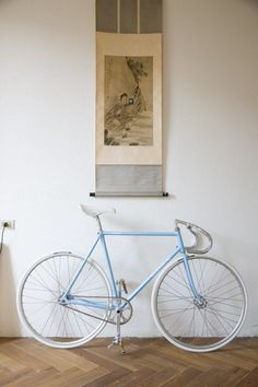 Baby blue frame fixed gear. White seat and tires with drop bars.