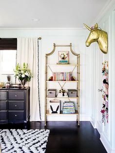 Jessica Alba - Fantastic big girl's room boasts a black dresser placed under a window dressed in black pom pom curtains, The Emily + Meritt Natural Linen Pom Pom Blackout Drapes, next to a gold etagere, PB Teen Maison Bookcase alongside a gold unicorn head, The Emily + Meritt Unicorn Wall Mount.
