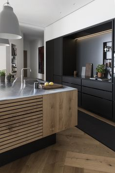 Black and natural wood contrast. Large herringbone wood floor. Cabinet lighting