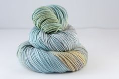 Sutherland DK  75% Fine superwash Merino, 20% silk, 5% silver Stellina  Double Knit, 100g skeins, 211 metres per 100g.  Colour - variegated silver, duck egg, soft moss, mustard  Hand wash recommended, dry flat  This is a One-Of-A-Kind colourway! No repeats...