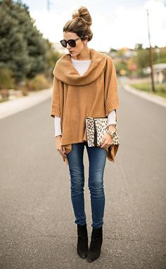 The versatility of a tan knit poncho and navy slim jeans makes them investment-worthy pieces. Why not introduce dark brown suede ankle boots to the mix for an added touch of style?  Shop this look for $215:  http://lookastic.com/women/looks/sunglasses-long-sleeve-t-shirt-poncho-clutch-watch-skinny-jeans-ankle-boots/6096  — Black Sunglasses  — White Long Sleeve T-shirt  — Tan Knit Poncho  — Beige Leopard Leather Clutch  — Gold Watch  — Navy Skinny Jeans  — Dark Brown Suede Ankle Boots
