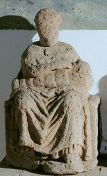 Figura femminile seduta su trono con bambino in fasce sulle ginocchia. La figura è rappresentata con il busto leggermente volto di tre quarti a sinistra con le gambe divaricate e con il bambino al seno in atto di poppare. Museo Provinciale Campano, Capua