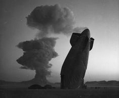 At a Nevada nuclear test site test Site, on August 7, 1957, the tail of a U.S. Navy Blimp is photographed with the cloud of a nuclear blast ...