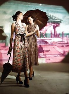 Dorian Leigh and Meg Mundy in print dresses standing in front of a background painted by Eugene Berman, photo by Serge Balkin, 1947