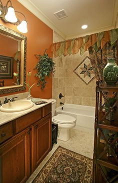 What do you think about the orange accent wall? This neutral stone tile shower has a white tub, recessed lights, oil rubbed bronze hardware and a tapestry shower curtain. Click to see how much it costs to add a shower to a freestanding tub.