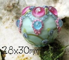 This LARGE ornate focal with a floral vine on a pale emerald base (I promise- it looks blue, but is a light green :) ). Bright fuchsia bubble jewels