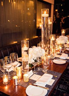 Candles floating in various tall glass vases makes a huge centerpiece statement.