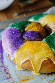 """King cakes are made around the world as part of the festival of the Epiphany, but in New Orleans, king cakes have truly taken on a life of their own. From the start of Carnival on January 6 through Mardi Gras at the beginning of February, you'll find one of these sweet, color-splashed king cakes in just about every office break room and at every family gathering. Did you get """"the baby""""? That means you bring the next cake — and we have just the cake you'll want to bring."""
