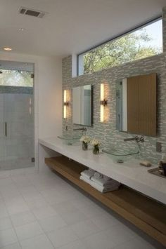 This bathroom has a wonderful feel: natural light from the clerestory window, while maintaining privacy, vanity with open shelving below, and glass tile focal wall.