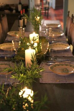 White or cream candles & greenery. Simple & elegant table top.