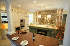 Custom Kitchen with beautiful islands and stacked rock surround above cooktop - WOW!