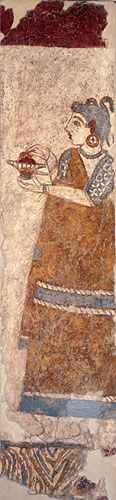 The priestesses were female, and Minoan religion was matriarchal with an all-powerful mother goddess.   This Minoan priestess from Akitori on Santorini has a head which is mostly shaven and lips and ears which are painted red. She holds a fire-box and appears to be adding incense to the fire.