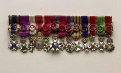 Van Wielik BV   Miniatuur ordetekens van Willem Drees, Van Wielik BV, 1950 - 1988   Speld met dertien miniatuur ordetekens (behorend bij de grootkruizen) van Willem Drees om op kostuum te dragen. De volgorde van links naar rechts is: Nederlandse leeuw LIB 1 = Grand Cross of the Order of Leopold of Belgium DD 1 = Grand Cross of Order of Dannebrog, of Denmark HDE 1 = Grand Cross of the Order of the Holy Trinity of Ethiopia LEF 1 = Grand Cross of the Order of the Légion d'Honneur of France Orde…
