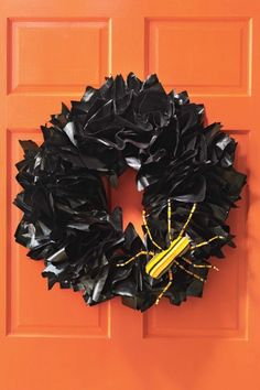 Halloween Newspaper Wreath Tutorial: A shiny black wreath fashioned out of spray-painted newspaper is a clever—and easy—way to welcome trick-or-treaters.