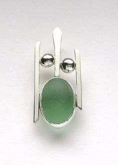 The green sea glass is genuine, it was found and supplied by.......  https://www.etsy.com/shop/mamzelleseaglass and is no back bezel set. The pendant is handmade of 14 gauge square sterling wire and melted sterling balls. It measures 5/8 x 1 1/2 inches and has a hidden bail.  GN868