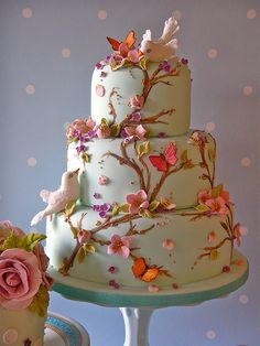 Three tier spring themed wedding cake with vines climbing up the cake, adorned with sugar paste flowers and butterflies, with two sugar white doves looking up and down at each other.  Bright colors for the flowers and butterflies
