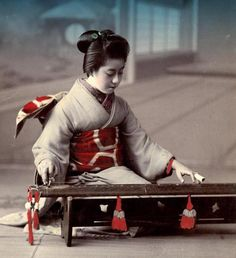 Geisha playing a yakumogoto - a two-stringed zither of the Oomoto Shinto sect.