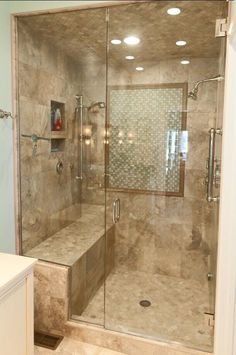 Check out this lovely tile shower we did. It has a nice bench seat and beautiful glass shower door with chrome fixtures.