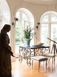 """Tara stood a statue from Avignon (""""probably 16th century—it's worm-eaten and petrified in the back,"""" she says) by the living room windows, which look out on a saltwater pool. Eighty trees line the property's perimeter, giving it a sense of privacy."""
