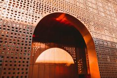 The walls of the copper volume were perforated with small squares that allow light to filter through the walls into the interior corridors.