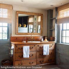 Dieses Badezimmer besticht durch seinen gemütlichen Landhaus-Charme: Ein rustikaler Waschtisch mit einer Armatur aus Messing und ein goldfarbener…