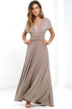 """As Seen On Nicholl of The Chiffon Diary blog! Versatility at its finest, the Tricks of the Trade Taupe Maxi Dress knows a trick or two... or four! Two, 73"""" long lengths of fabric sprout from an elastic waistband and wrap into a multitude of bodice styles including halter, one-shoulder, cross-front, strapless, and more. Stretchy, latte brown jersey knit hugs your curves as you discover new ways to play with this fascinating frock. Full, maxi-length skirt has a raw hemline. Want Styling Tips?…"""
