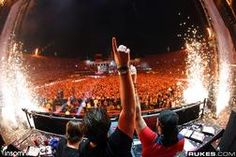 Picture of Swedish House Mafia in concert. This trend of electronica bass driven music focusing on tempo changes, has been adopted from the current spirit of the times in Europe. This zeitgeist has created numerous concerts where people spray paint on each other and wear all white clothes to reflect neon lights. In addition, this music inspires people to be expressive as fashion does.Here we can see that this spirit of the times in upbeat music has inspired the fashion trends of today…