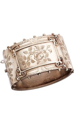 Wide silver bangle bracelet with engraved floral pattern and beaded detail at edges of face, 1880.