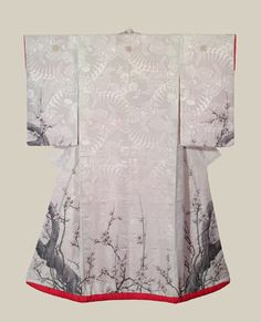 """This unusual and stunning silk antique uchikake features a rinzu (damask) base, with large fan and paulownia motifs. The main design consists of wonderful yuzen-dyed plum blossom motifs. The mon (family crest) and other highlights are finely embroidered. 48"""" from sleeve-end to sleeve-end x 62"""" height. The style and imagery on this uchikake resembles that on an early 19th century kimono designed by the artist Sakai Hoitsu (see page 184 of When Fashion Became Art).  The Kimono Gallery"""