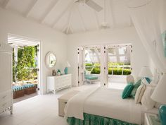 Follett's master bedroom enjoys gentle cross breezes. The entire home is whitewashed with anchoring blue tones.
