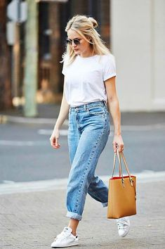 Look básico e cool com óculos redondo, camiseta branca, mom jeans claro, tênis stan smith branco e bolsa bege