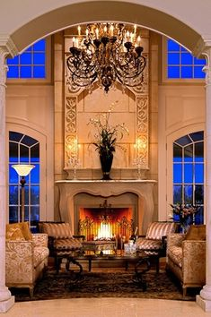 Living Room with stone tile floors, travertine tile floors, Fireplace, Arched window, Chandelier, Columns