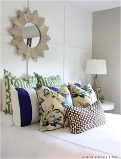 Patterned pillows and a bold mirror spice up this bedroom decor.