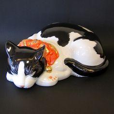 眠り猫白黒(大)(ねむりねこしろくろ(だい)) 21,000円  横幅 34cm 奥行 20cm 高 13cm    本物の猫と同じほどの大きさの眠り猫です。全体は白黒の日本猫の絵付けにして、首輪だけが明るい盛絵付けを施してあります。紙製の箱に入れてお届けします。
