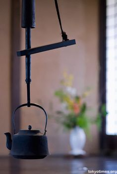Japanese iron tea kettle (tetsubin) hung on a jizaikagi.