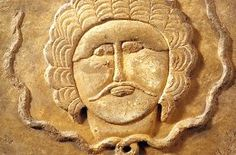 Fragment of a human face in stone, framed by a row of curls, from Museum of Zafar.