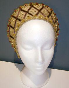 Tipico copricapo alla francese in damasco con motivi intrecciati in velluto rosso e pietre dure applicate. Costo £80
