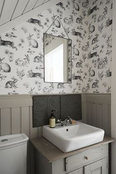 Old farmhouse bathroom with new fixtures and bunny wallpaper.