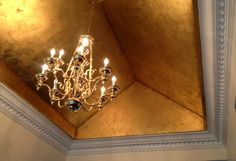 We gilded this foyer ceiling in a gold leaf schabin and then antiqued it. This treatment made for an exciting entry into this beautiful home.