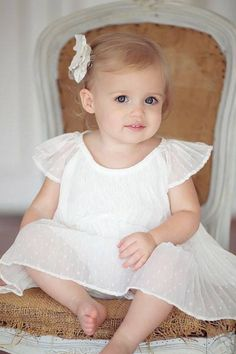 Adorable little girl in her pretty white dress.
