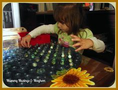 An easy and budget friendly Toddler Fine Motor Activity with marbles and a mat!