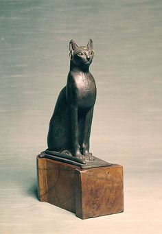Egyptian - Statue of a Seated Cat - Walters 54403 - Three Quarter.jpg This seated cat has golden earrings, a golden scarab inlaid on the forehead, and a necklace with a pendant in low relief. The Walters Art Museum.