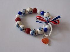 Armband in Hollands Glorie stijl. Met rood-wit-blauwe kralen, 1 oranje hartje en delftsblauwe kralen met bloemetjes. Gemaakt van elastiek en ca. 20 cm lang.