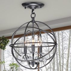 This Benita three-light flush mount chandelier is crafted of iron and finished in antique bronze to add depth and dimension to the fixture. The spherical shade is finely designed with overlapping rings that allow the light to softly filter through.
