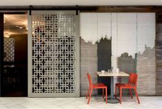Love  over sized screen-doors designed with geometric Chinese patterns and the interesting texture art against the simple bistro table and seats - Julians' cafe, Dallas