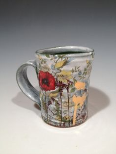 Justin Rothshank  |  Cup with layered green glaze, poppies, and gold decals.