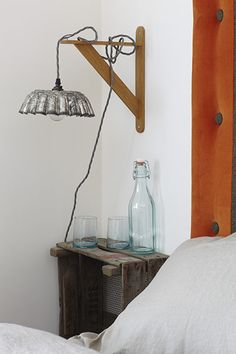 Old bulb crates are wall-mounted as bedside tables – try Hen and Hammock for similar. Above them, brioche tin lights hang from wooden shelf brackets. Re-Found sells lights made from vintage jelly moulds and colanders.