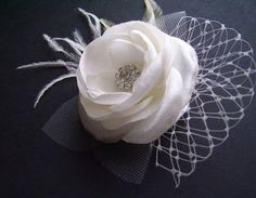 This bridal hair flower is made with multiple layers of satin, feathers, french veil and beautiful gems.Size approximately: the flower 6cm, 12 cm with feathers.