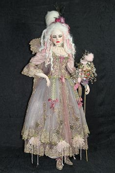 """Marquise Barbarella"" by Sylvia Weser. Made from white Limoges porcelain and is 39"" tall. She has a white mohair wig and purple crystal glass eyes, mouth blown in Germany.  Her body is made from leather and has an armature inside, so the doll is poseable. Her costume is made from rare antique fabrics, embroidered with golden threads, crystals and tiny pearls."