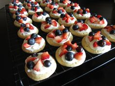 """4th of July Mini Fruit Pizzas. For the """"crust,"""" roll Pillsbury sugar cookie dough into 3/4"""" balls and bake at 350. For the """"sauce,"""" mix 1 block softened cream cheese; 7 oz. marshmallow fluff; and 1 cup powdered sugar until smooth. Spread on cookies. Top with blueberries and chopped strawberries. #4thofjuly #patriotic"""